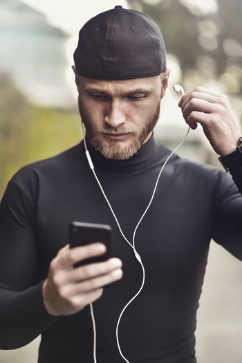 Close-up shot of young white man with beard putting headphone in his ear. Determined sportsman is ready for long-distance run and workout Athlete wearing sport fitness tracker and headphones.