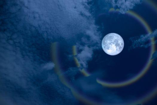 full flower halo moon and rainbow on night sky