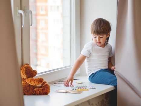 Toddler sits on windowsill and plays with scattering pills without parent's control. Dangerous situation with little boy. Medicines are freely available to child.