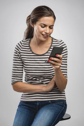 Beautiful happy young woman sitting on a bench and sending a text message to someone