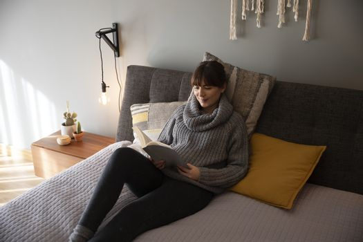 Beautiful woman on bed and reading a book