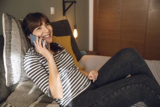 Woman on her bedroom, having a great chat at phone