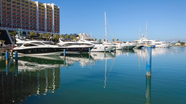 Luxury yachts moored in the port of Vilamoura at the hotel building, Algarve, Portugal