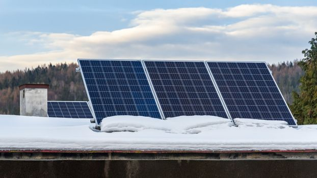 Solar panels of photovoltaic power plant on the snow covered roof