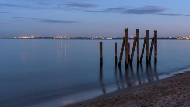 Wooden piles in the Gulf of Gdansk at the beach in Gdynia Orlowo in Poland at dusk