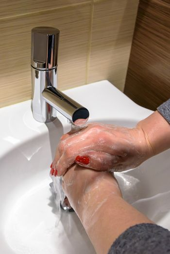 A woman is soaping her hands with soap under running water