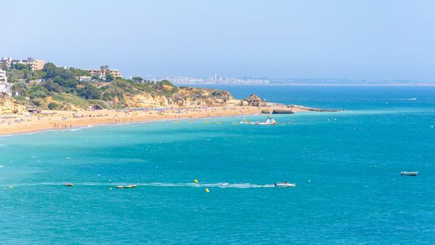 View of beach in Albuferia with Vilamoura town in the background, Algarve, Portugal