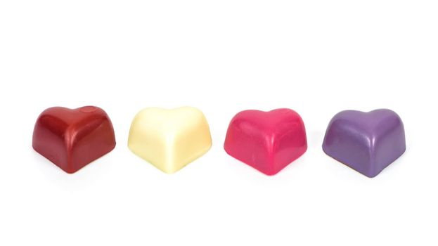 Colorful heart shaped chocolates in a row isolated on white background with clipping path