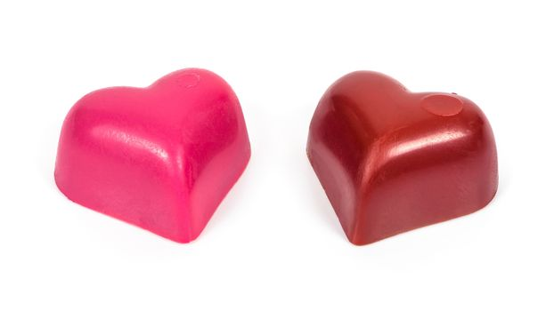 Two heart shaped chocolates in a row isolated on white background with clipping path