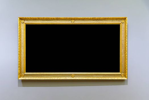 Empty golden picture frame on the gray wall
