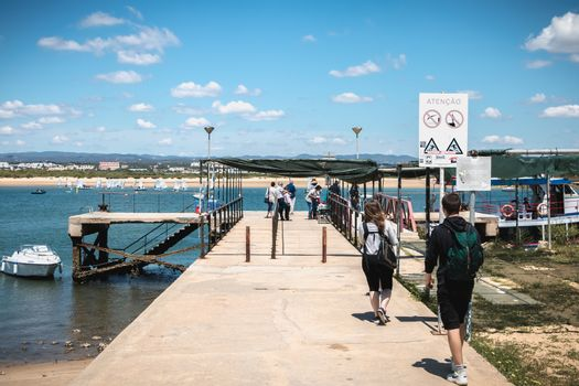ilha de tavira, portugal - may 3, 2018: people riding in a taxi boat on the island towards the continent on a spring day