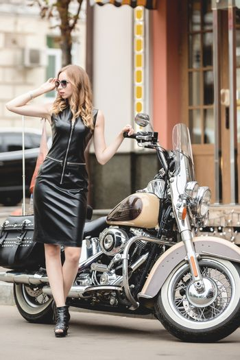 Sexy young woman near old fashioned custom motorcycle. Outdoor lifestyle portrait