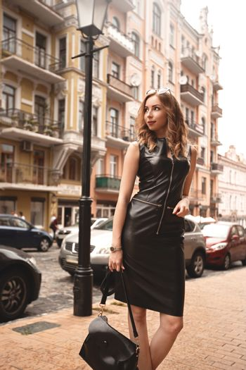 Stylish, luxurious girl in a chic black dress on the street, female with fashion makeup near the building, black dress on tall woman with long legs walks in the city.
