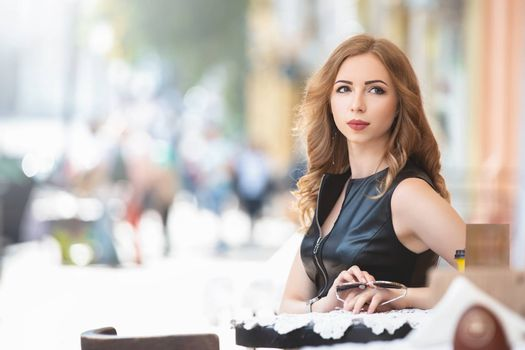 Attractive young caucasian woman sitting in street cafe, waiting for someone, having coffee, having great time. She wearing black stylish dress,
