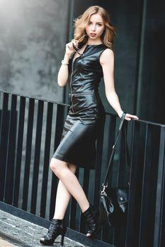Portrait of curly woman in black dress on a street