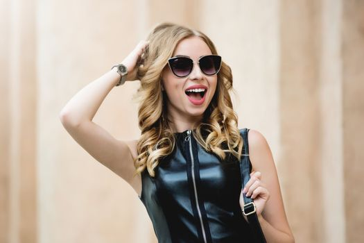 portrait of glamorous woman with glasses dressed in a black stylish dress after shopping. shopping time concept