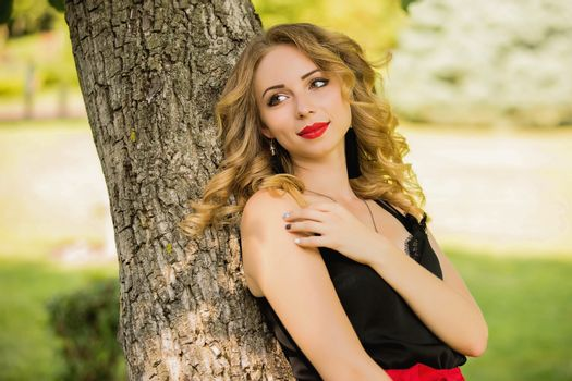 portrait of beautiful young smiling woman in red shorts posing in a park near a tree