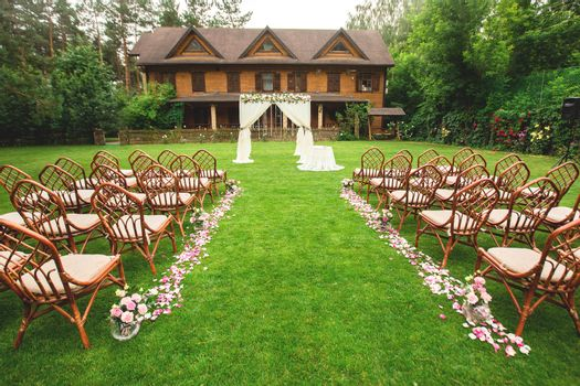 Outdoor wedding ceremony decoration setup. Path with petals, chairs decorated with colorful ribbons, white arch. wedding concept