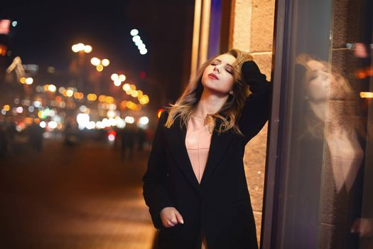 portrait of Beautiful young woman in black on a background of a night city. night life