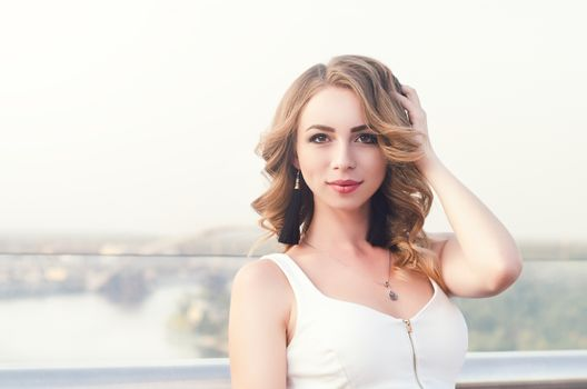 Portrait of beautiful white Caucasian girl woman with long hair outside in city street bridge, looking in camera, lifestyle portrait concept