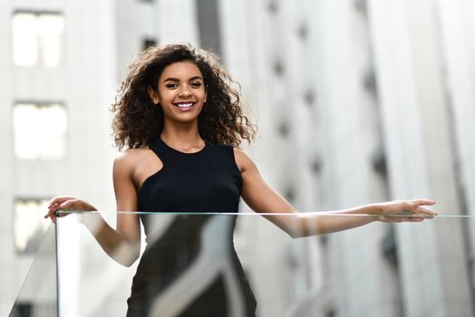 Young attractive mixed race girl with beautiful afro hair who is smiling and Looks into the camera at the street