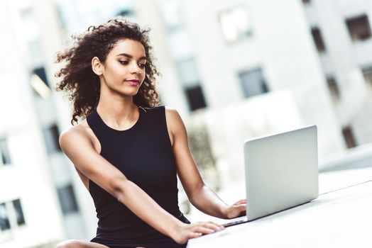 Young attractive mixed race girl with beautiful afro hair who is smiling looking at her laptop screen during video call. Young woman using laptop.
