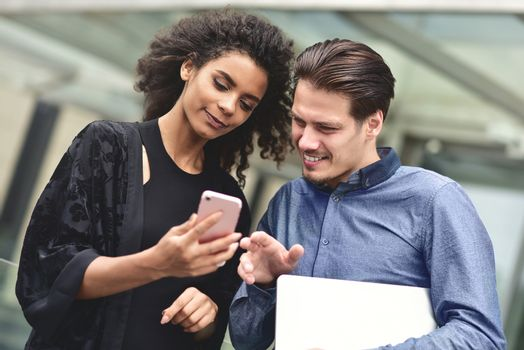 Business man and woman looking at smartphone together on building background in city outdoor feeling happy.