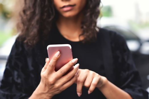 Close up portrait of beautiful young african american woman reading text message on mobile phone at street.