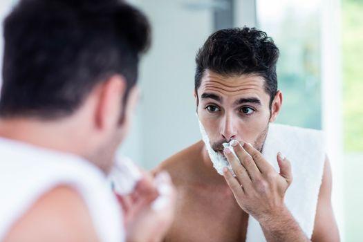 Handsome man shaving his beard