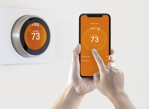 A person using a smart phone application warming up the room temperature with a wireless smart thermostat on a white background.