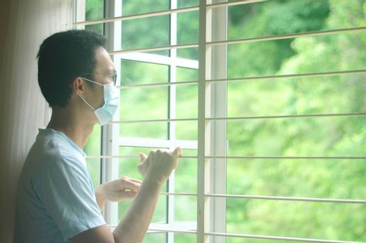 Sick man of corona virus looking through the window and wearing mask protection and recovery from the illness in home. Patient isolated to prevent infection.