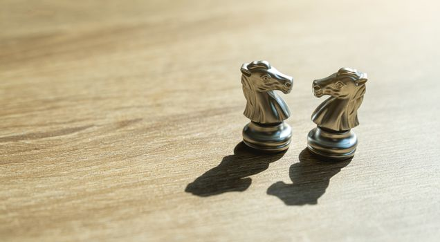 Two golden horse chess together with shadow in concept, business, negotiation, success and competition On board chess with a selective space copy on wodden table