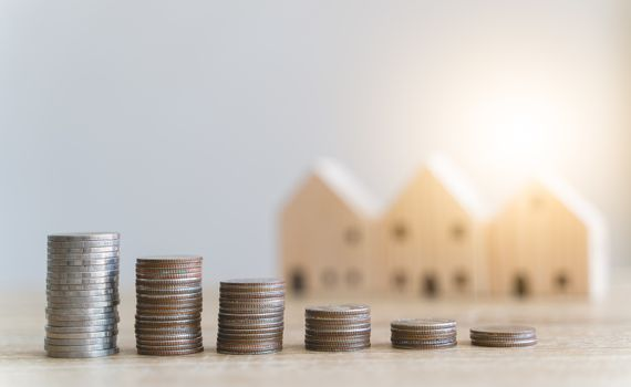 Money savings concepts. Stacked coins with blur wooden house in meaning about saving money to buy a house, refinancing, investment or financial on wooden table with blur background and copy space