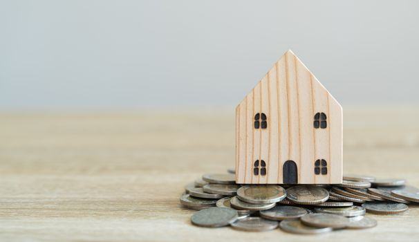 Money savings concepts. Wooden house models with coins in meaning about saving money to buy a house, refinancing, investment or financial on wooden table with blur background and copy space
