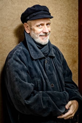 Portrait of a mature smiling man with a white beard and a cap on the head. He could be a sailor, a worker, a docker, or even a gangster or a thug. He has a penetrating gaze.