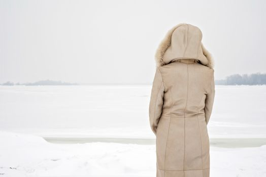 A woman with a leather coat with a fur hood is looking at the frozen Dnieper river during a cold and sad gray winter morning under the snow