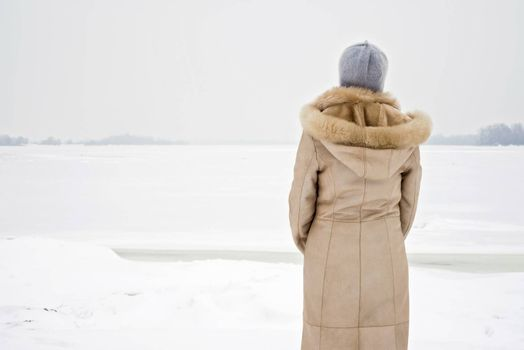 A woman with a wool cap and a leather coat is looking at the Dnieper river during a cold and sad gray winter morning under the snow