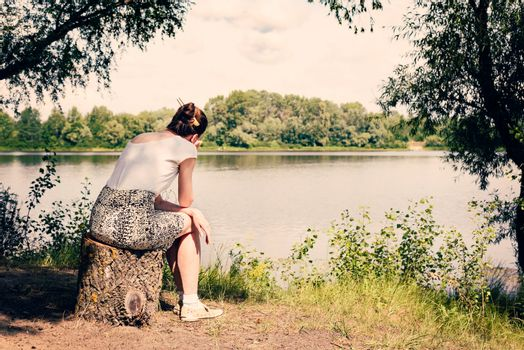 A sad and nostalgic woman is sitting close to the Dnieper river in Kiev, Ukraine. She is thinking while watching or observing far in the distance, under a warm and soft summer sun