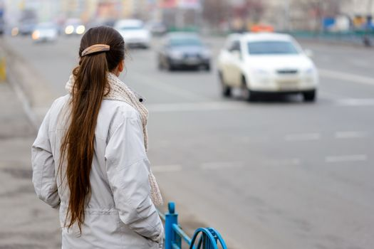 A woman with a ponytail stands, waiting or watching, close to the street with cars in the city