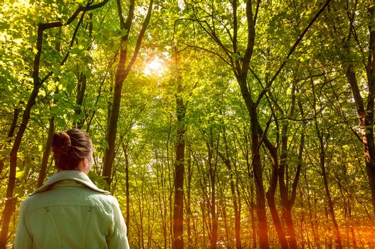 A woman lightened by the sun rays through the tree in a deep forest