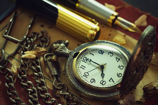 Vintage pocket watch and brass pen on old book. At 8 o'clock in morning. Education and vintage style concept.