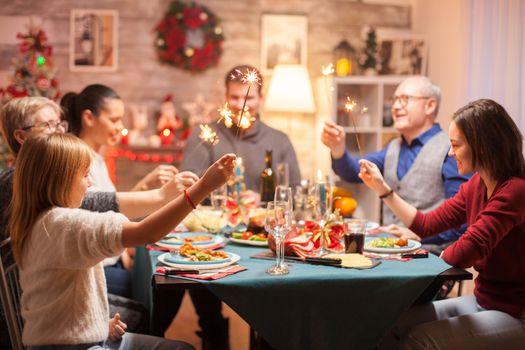 Cheerful senior man at christmas family dinner holding hand fireworks.
