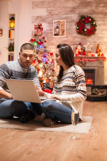 Romantic couple buying gifts from laptop using laptop for christmas.