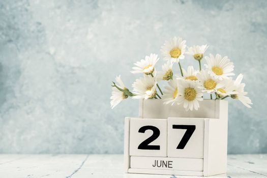 White cube calendar for june decorated with daisy flowers over blue background with copy space