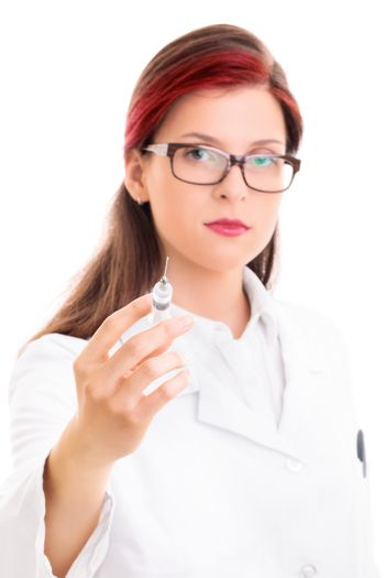 Close up of a young serious female doctor with glasses holding a syringe with needle, isolated on white background. Health care concept.