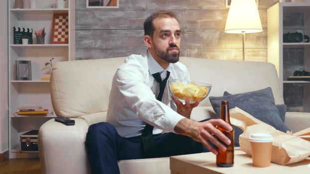 Businessman in formal ear sitting on couch eating chips