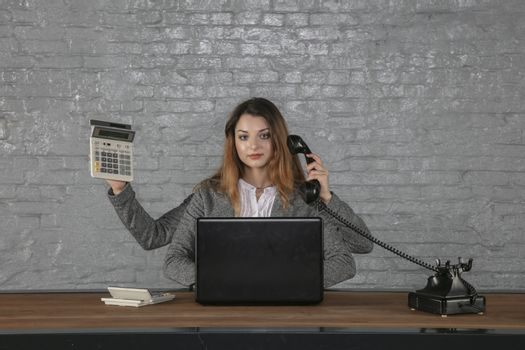 Young multitasking business woman sitting at desk