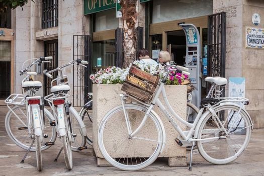 Valencia, Spain - June 16, 2017: Verrassend Valencia rental bicycle parked on a small tourist square in the historic city center on a summer day