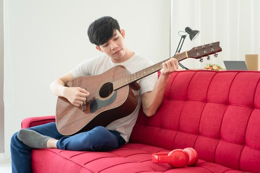A young Asian man is at home happily. He is unemployed He is playing guitar and singing to relax.