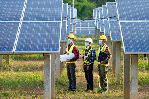 Engineer wearing protective mask to Protect Against Covid-19  working on checking and maintenance in solar power plant,Solar power plant,Science solar energy.